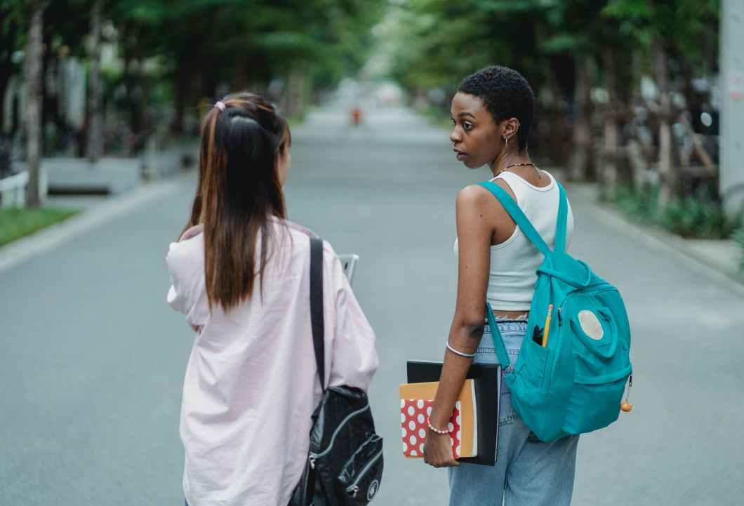 multiethnic girlfriends walking together after studies